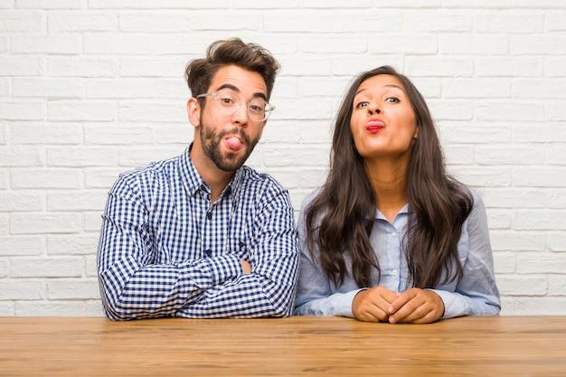 Jovem mulher indiana e homem caucasiano casal expressão de confiança e emoção, divertido e amigável, mostrando a língua como um sinal de jogo ou diversão Foto Premium