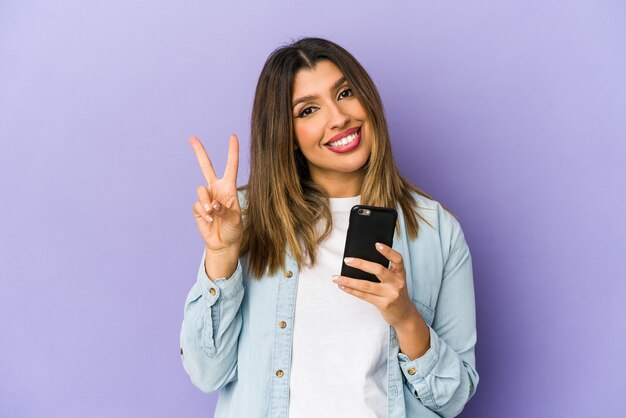 Jovem mulher indiana segurando um telefone mostrando o número dois com os dedos. Foto Premium