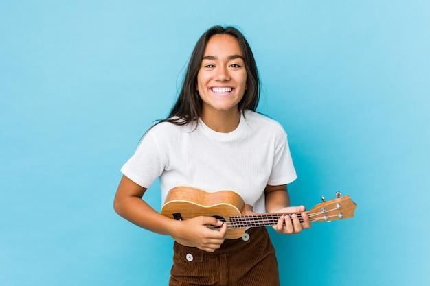 Jovem mulher indiana tocando ukelele feliz Foto Premium