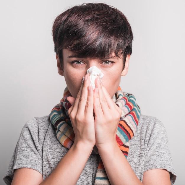 Jovem mulher indisposta assoar o nariz contra o fundo cinza Foto Premium