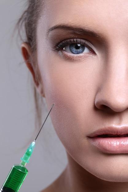 Jovem mulher injetando um tratamento de beleza Foto gratuita
