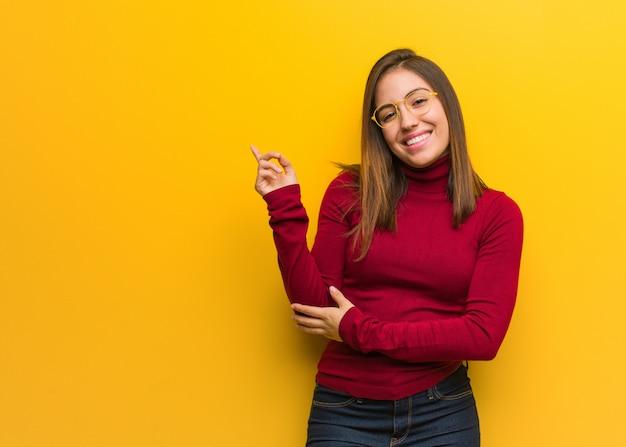 Jovem mulher intelectual apontando para o lado com o dedo Foto Premium