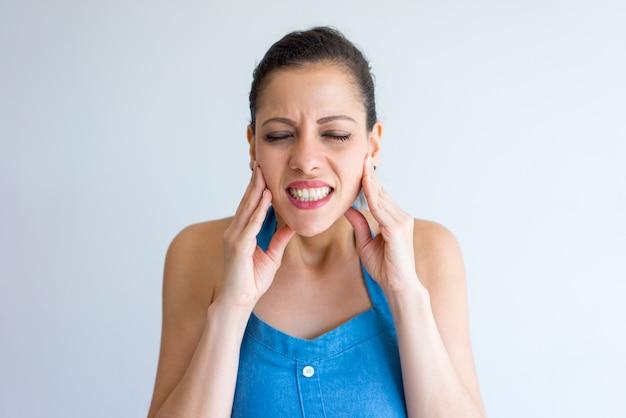 Jovem mulher irritada que sofre da dor de dente e que toca na maxila. Foto gratuita