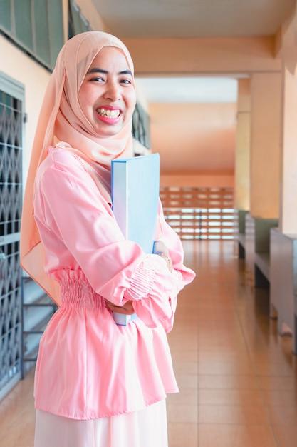 Jovem mulher islâmica. ela está de pé na varanda no escritório. ela é sorriso e segurando docume Foto Premium