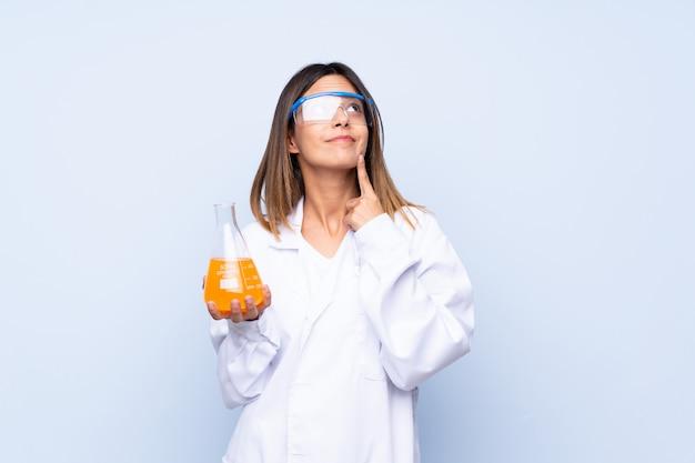 Jovem mulher isolada parede azul com um tubo de ensaio científico Foto Premium