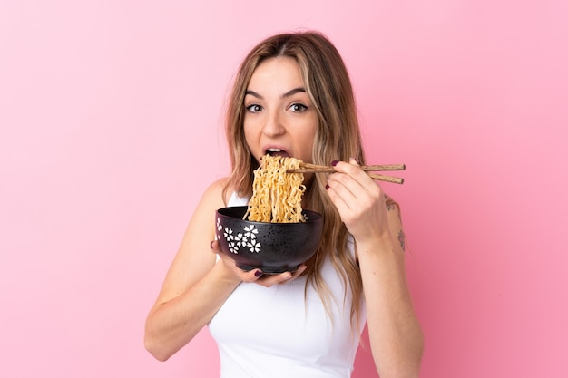 Jovem mulher isolada parede rosa segurando uma tigela de macarrão com pauzinhos e comê-lo Foto Premium