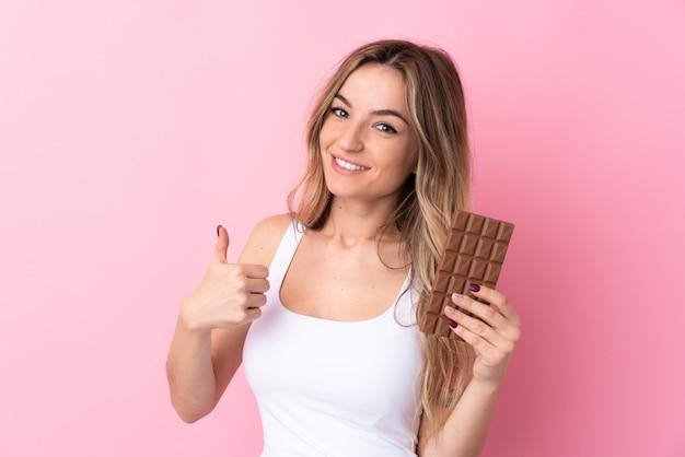 Jovem mulher isolada parede rosa tomando uma tablete de chocolate e com o polegar Foto Premium