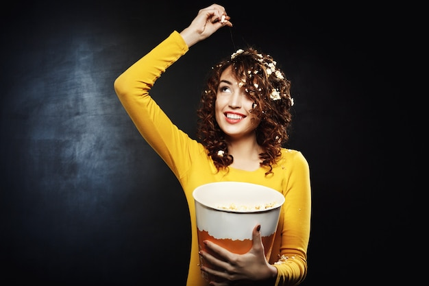 Jovem mulher jogando pipoca olhando com sorriso largo a sorrir Foto gratuita