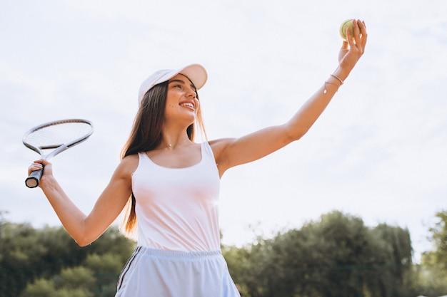Jovem mulher jogando tênis na quadra Foto gratuita