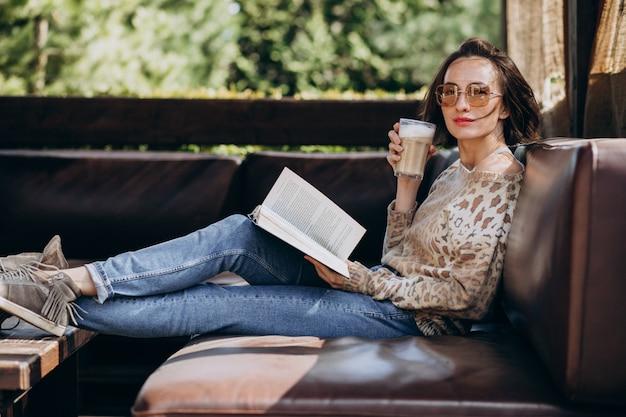 Jovem mulher lendo livro e bebendo café Foto gratuita