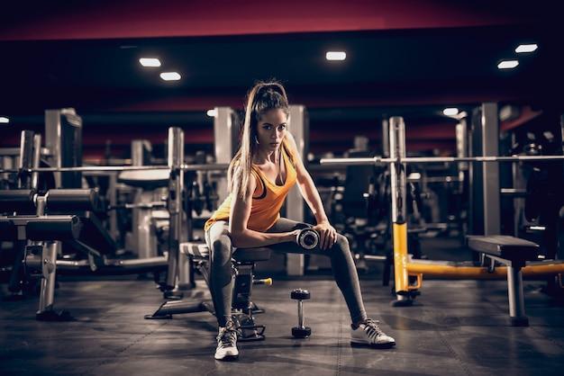 Jovem mulher levantando pesos e sentado no banco enquanto olha para a câmera. luz lateral, interior do ginásio. Foto Premium