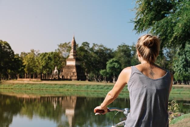 Jovem mulher loira andando de bicicleta olhando a arquitetura na natureza, em sukhotai tailândia Foto Premium