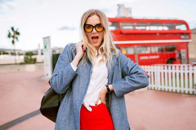 Jovem mulher loira bonita caminhando no centro da cidade de londres, vestindo roupa elegante elegante estudante casual inteligente, casaco azul e óculos coloridos, outono primavera tempo de meia temporada, clima de viagem. Foto gratuita