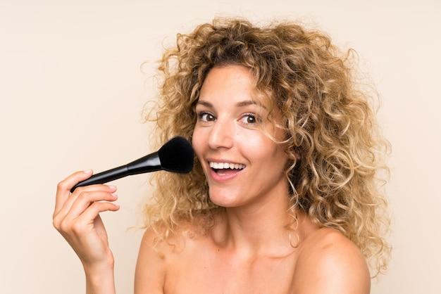 Jovem mulher loira com cabelos cacheados com pincel de maquiagem Foto Premium