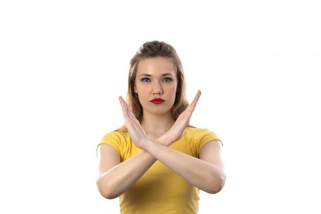 Jovem mulher loira com camiseta amarela diz não com os braços Foto gratuita