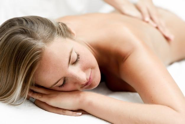 Jovem, mulher loira, com massagem no salão de spa Foto gratuita