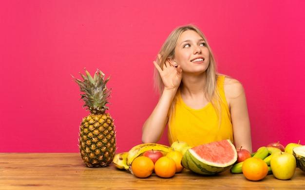 Jovem mulher loira com muitas frutas, ouvindo algo Foto Premium