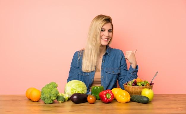 Jovem mulher loira com muitos legumes apontando para o lado para apresentar um produto Foto Premium