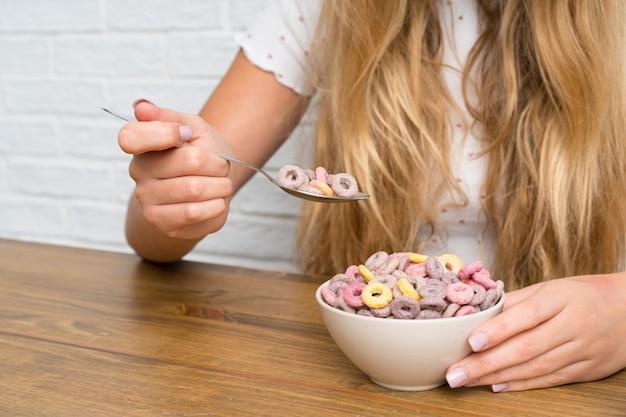 Jovem mulher loira com uma tigela de cereais Foto Premium