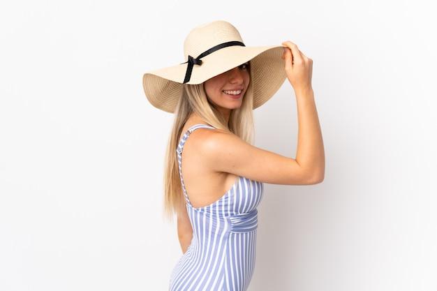 Jovem mulher loira isolada na parede branca em traje de banho nas férias de verão Foto Premium