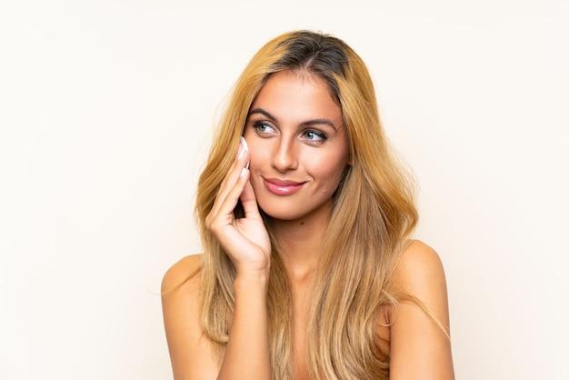 Jovem mulher loira removendo maquiagem do rosto com almofada de algodão Foto Premium