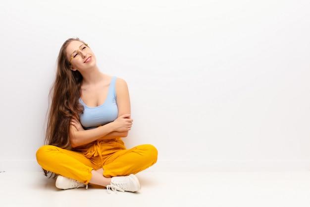 Jovem mulher loira se sentindo feliz, orgulhosa e esperançosa, pensando ou pensando, olhando com os braços cruzados, sentado no chão Foto Premium