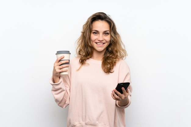 Jovem mulher loira segurando café para levar e um celular Foto Premium
