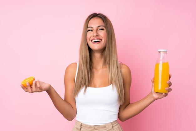 Jovem mulher loira segurando uma laranja Foto Premium