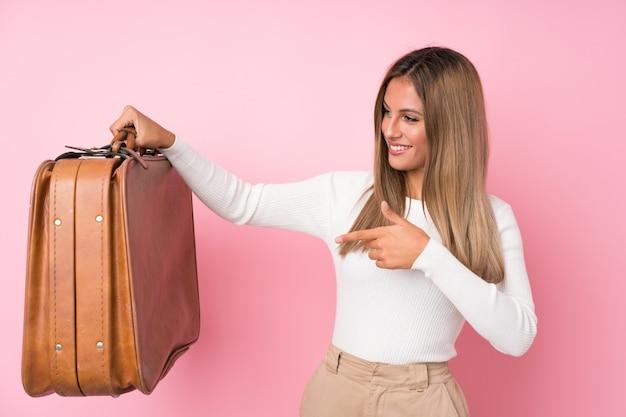 Jovem mulher loira segurando uma mala vintage Foto Premium
