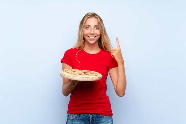 Jovem mulher loira segurando uma pizza sobre parede azul isolada apontando uma ótima idéia Foto Premium