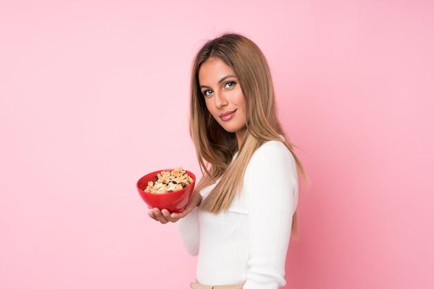 Jovem mulher loira sobre fundo rosa isolado, segurando uma tigela de cereais Foto Premium