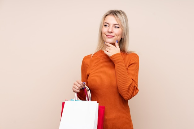 Jovem mulher loira sobre parede isolada segurando sacolas de compras e pensando Foto Premium