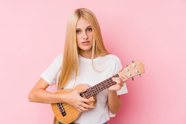 Jovem mulher loira tocando ukelele isolado em uma parede Foto Premium