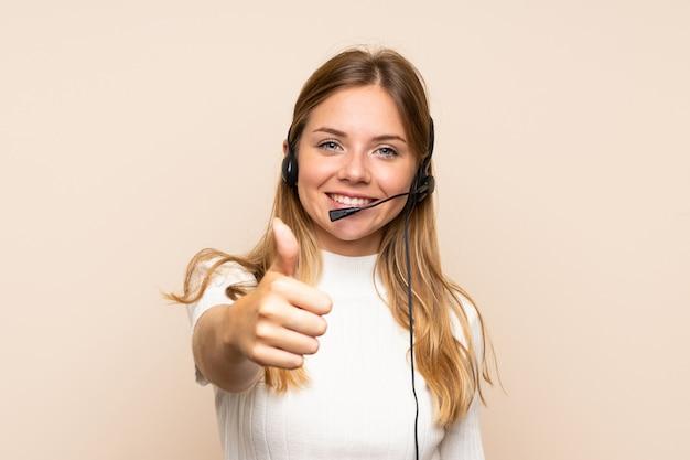 Jovem mulher loira trabalhando com fone de ouvido com o polegar para cima Foto Premium