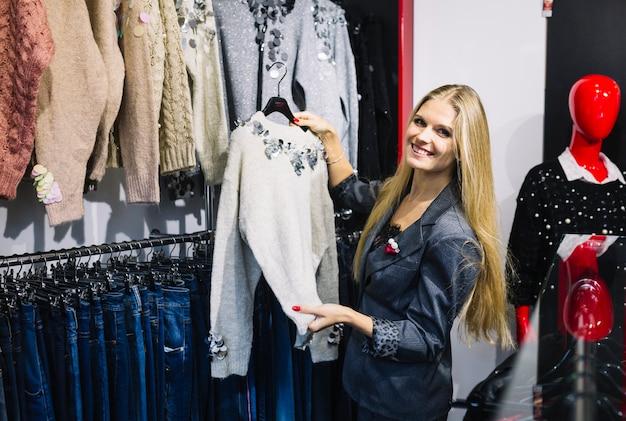 Jovem mulher loura de sorriso que escolhe a camisola cinzenta na loja Foto gratuita