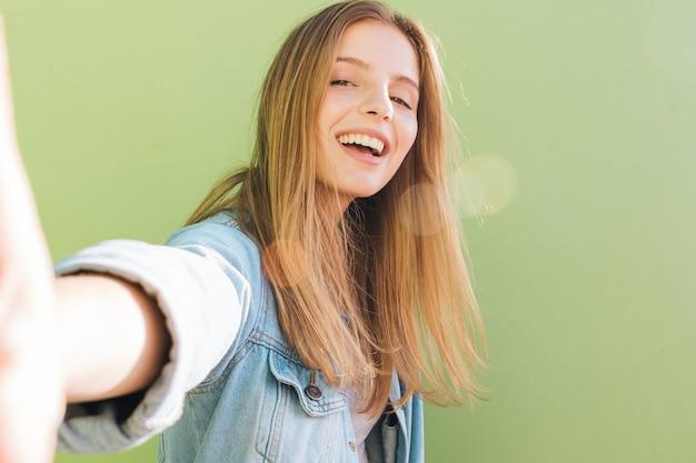 Jovem mulher loura de sorriso que toma o selfie contra o fundo verde da hortelã Foto gratuita