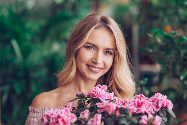 Jovem mulher loura feliz que está atrás das flores cor-de-rosa com fundo borrado Foto gratuita