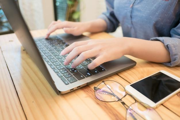 Jovem mulher mãos digitando o computador portátil no café Foto Premium