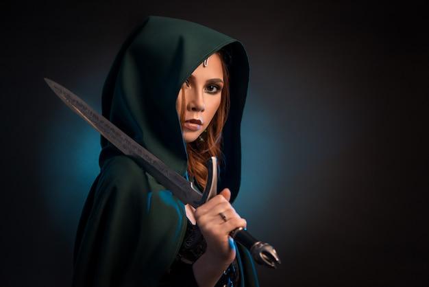 Jovem mulher misteriosa que mantém a faca afiada, vestindo a capa verde com uma capa. Foto Premium