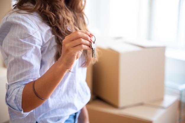 Jovem mulher mostrando ou dando a chave, posando em um apartamento novo com uma pilha de caixas de papelão no fundo Foto gratuita