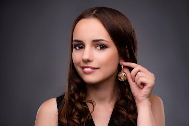 Jovem mulher mostrando seus brincos novos Foto Premium