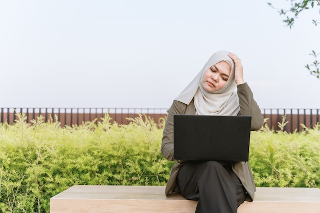 Jovem mulher muçulmana asiática no fato verde e trabalhando em um computador no parque. dor de cabeça de mulher e sentir dor. Foto Premium