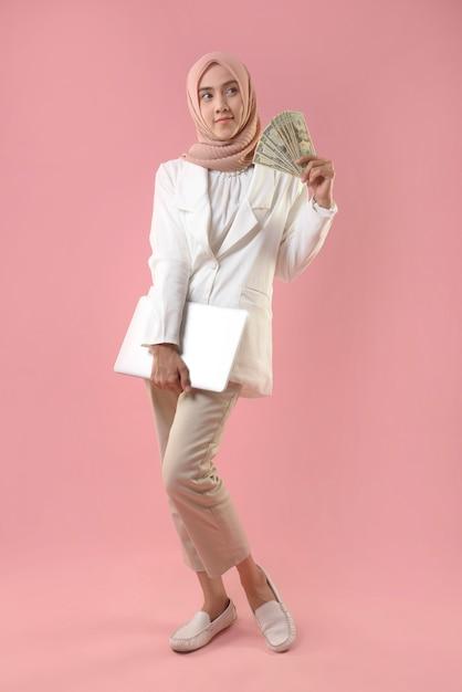 Jovem mulher muçulmana segurar dinheiro e laptop Foto Premium