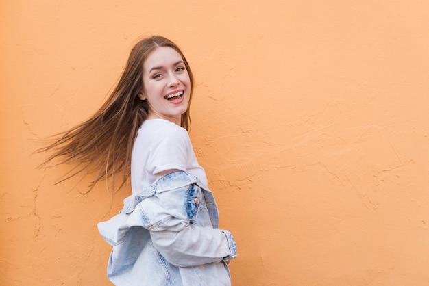 Jovem mulher muito bonita que levanta perto do fundo colorido da parede Foto gratuita