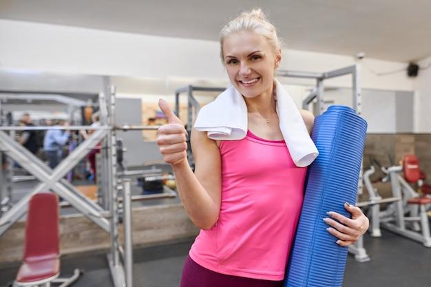Jovem mulher na academia, mostrando os polegares Foto Premium