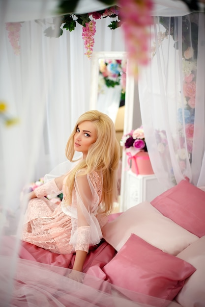 Jovem mulher na cama com flores Foto Premium