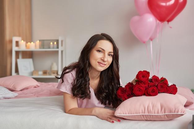 Jovem mulher na cama de pijama rosa com buquê de rosas vermelhas Foto Premium