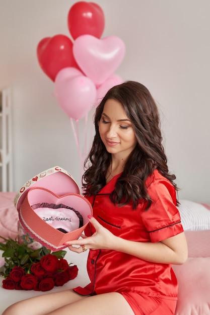 Jovem mulher na cama de pijama vermelho com caixa de presente em forma de coração Foto Premium