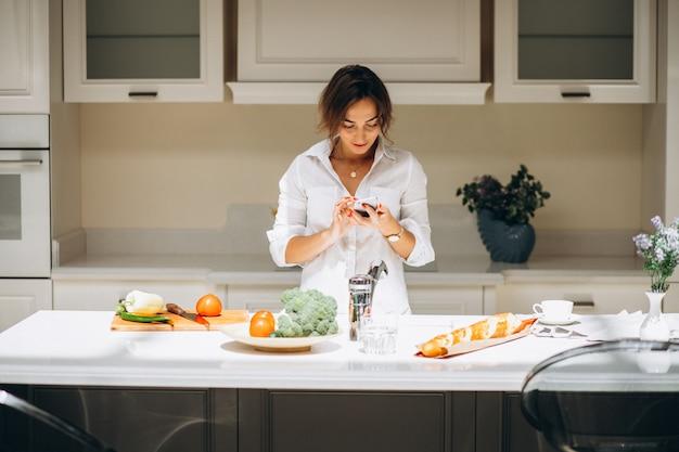 Jovem mulher na cozinha cozinhando o café da manhã e falando ao telefone Foto gratuita