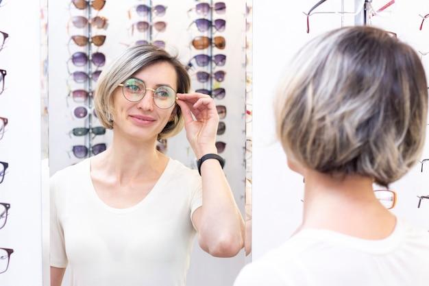Jovem mulher na loja de ótica, escolhendo novos óculos com oculista. óculos na loja de ótica. uma mulher escolhe óculos. emoções. oftalmologia. Foto Premium
